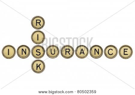 risk and insurance crossword in old round typewriter keys isolated on white