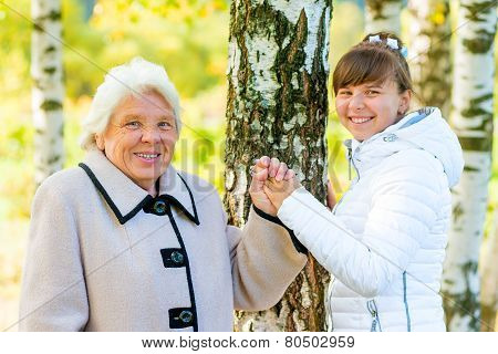 Grandmother And Granddaughter Walking In The Autumn Park