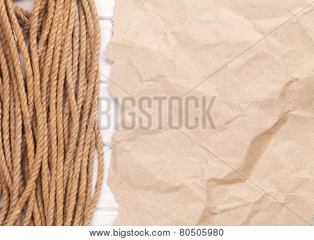 Brown rumpled cardboard paper background with marine rope and copy space