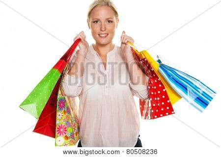 a young woman with colorful shopping bags while shopping. pleased with the deal.
