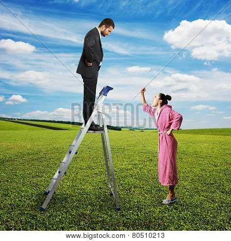 emotional woman screaming at serious man on the stepladder. photo at outdoor