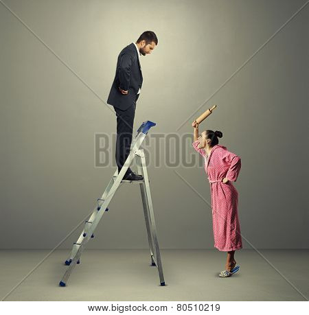housewife holding rolling pin and screaming at man on the stepladder over dark background