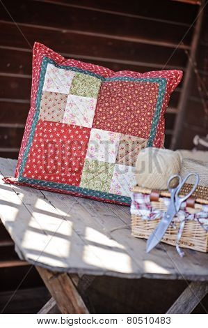 handmade quilt cushion and sewing tools on wooden table