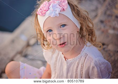 cute curly child girl portrait in pink flower headband