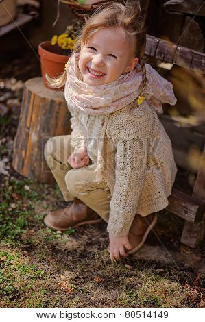 cute happy child girl with pigtails sitting near wood shed in country spring garden