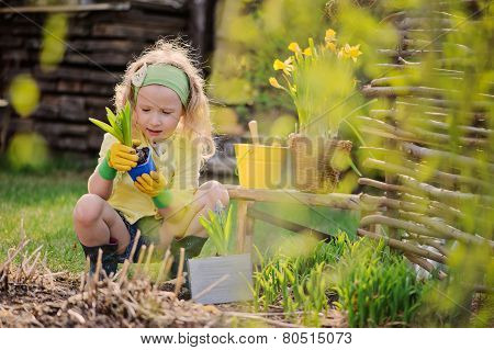 adorable happy child girl plays little gardener and planting flowers in spring garden