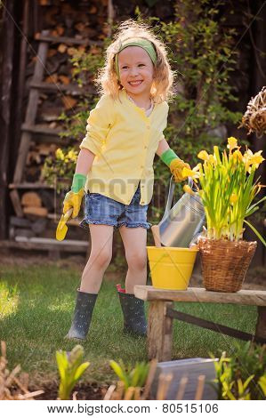 adorable happy child girl playing little gardener and holding watering can in spring garden