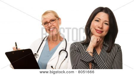 Hispanic Woman With Female Doctor Or Nurse