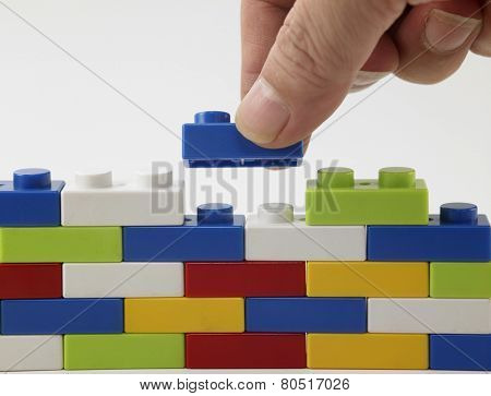 hand stack up lego set as a wall on white background