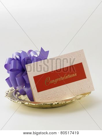 purple ribbon bow and a congraturation card