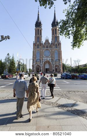 RADOM CITY, POLAND - August 8, 2014: Unidentified people walk in front of Catholic cathedral of the Protection of the Blessed Virgin Mary in Radom, Poland