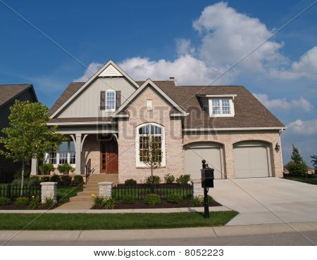 Small Beige Brick Home with Two Car Garage in Front