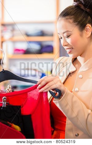 Woman choosing clothes on clothes rail in boutique or fashion store