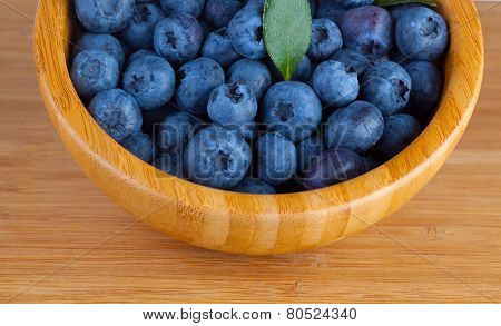 Blueberry berries in a wooden bowl on a table