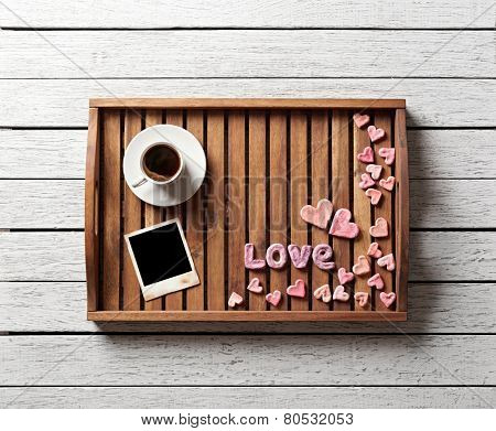 Cute valentine's items on salver: small hearts, blank photo frame, word love and cup of coffee.
