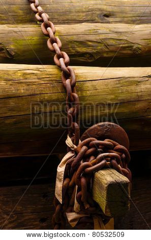Pile of wooden trunks secured with an old rusty link chain
