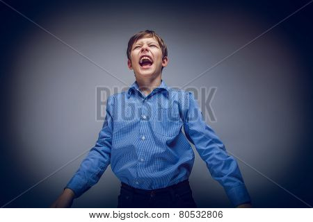 Portrait of a boy brown European appearance shouting on gray bac
