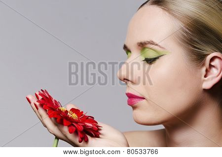fashion portrait of a blonde woman holding a flower