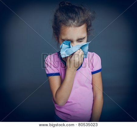 teen girl is sick sneezes handkerchief on a gray background cros