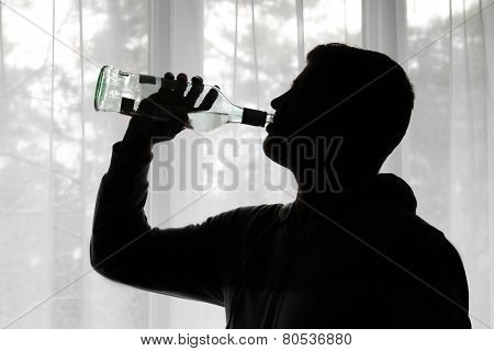 Alcoholism - Silhouette Of Man Drinking Alcohol