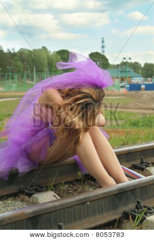 Beauty Girl Sitting On The Rail