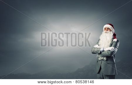 Businessman in Santa hat with arms crossed on chest
