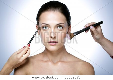 Closeup portrait of a woman applying dry cosmetic tonal foundation on the face using makeup brush