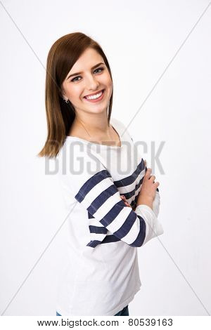 Portrait of a happy woman standing with arms folded over gray background
