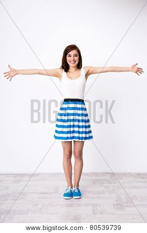 Full length portrait of a young happy girl glad to see you