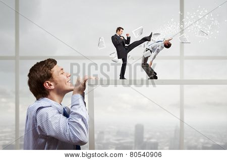 Businessman looking from under table at two fighting colleagues