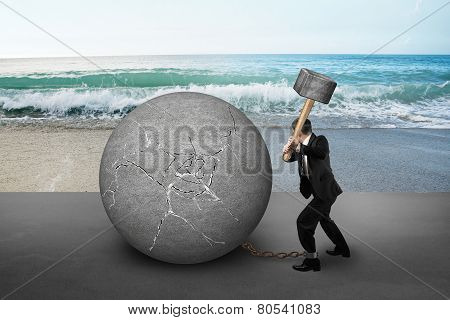 Businessman Holding Hammer Hitting Cracked Concrete Ball With Sea Beach
