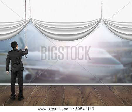 A Businessman Pulling Open White Blank Curtain Showing Airplane Sunlight