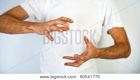Close up torso view of a man making a hand gesture to clasp a round object with his hands positioned top and bottom and fingers spread, blank space in between over his white t-shirt