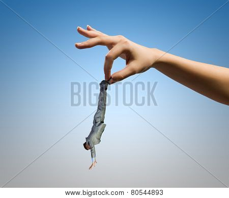 Close up of human hand holding miniature of businessman