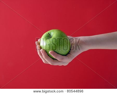Apple In Hand On Red