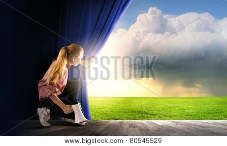 Young woman in casual with megaphone opening curtain