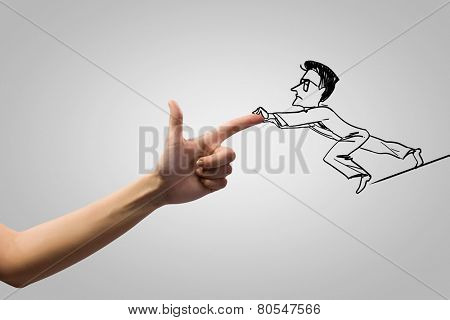 Close up of human hand attacking businessman caricature