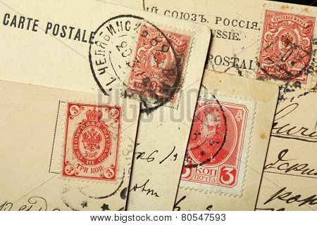 Tsar Alexander III of Russia and Russian double-headed eagles depicted in the Russian postage stamps on the old postcards.