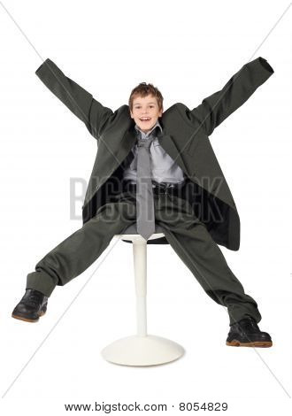 Little Boy In Big Grey Man's Suit Sitting On Chair And Smiling Isolated On White Background