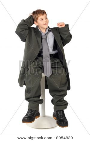 Little Boy In Big Grey Man's Suit Sitting On Chair Isolated On White Background