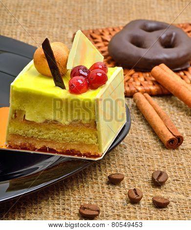 Yellow Cake With Cranberries On Black Saucer With Cinnamon Sticks
