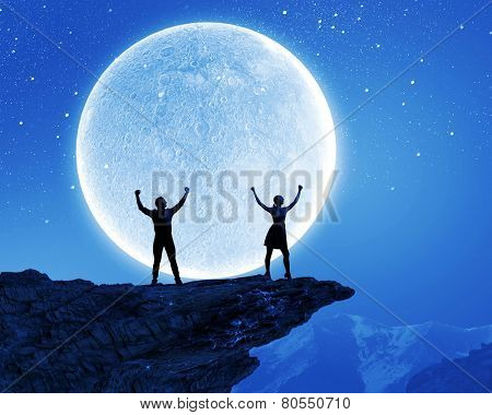 Silhouettes of young couple at night under big moon