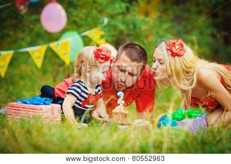 Young family celebrating birthday of his daughter in the park in the summer.