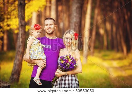 Young family walking in the woods in the summer.