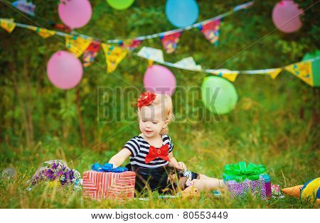 Birthday celebration of a little girl in the park in the summer.