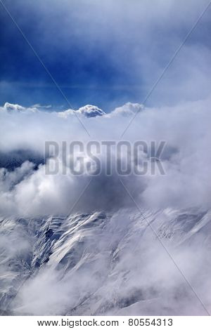 View On Off-piste Slope At Mist And Sunlight Clouds