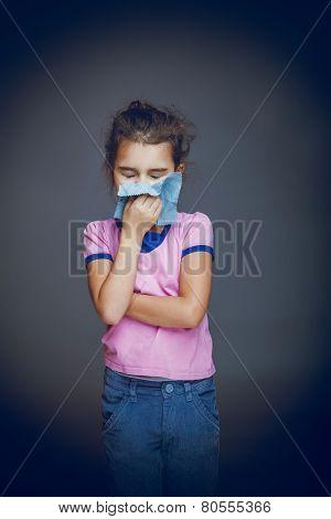 the girl child is sick in hands handkerchief on
