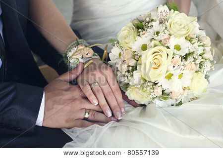 Bride And Groom's Hands With Wedding Rings And Bouquet Of Flowers