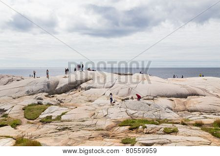 People Standing On Rocks At Peggys Cove