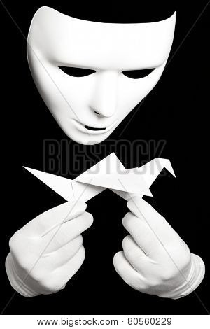 White theatrical mask and paper japanese crane isolated on black